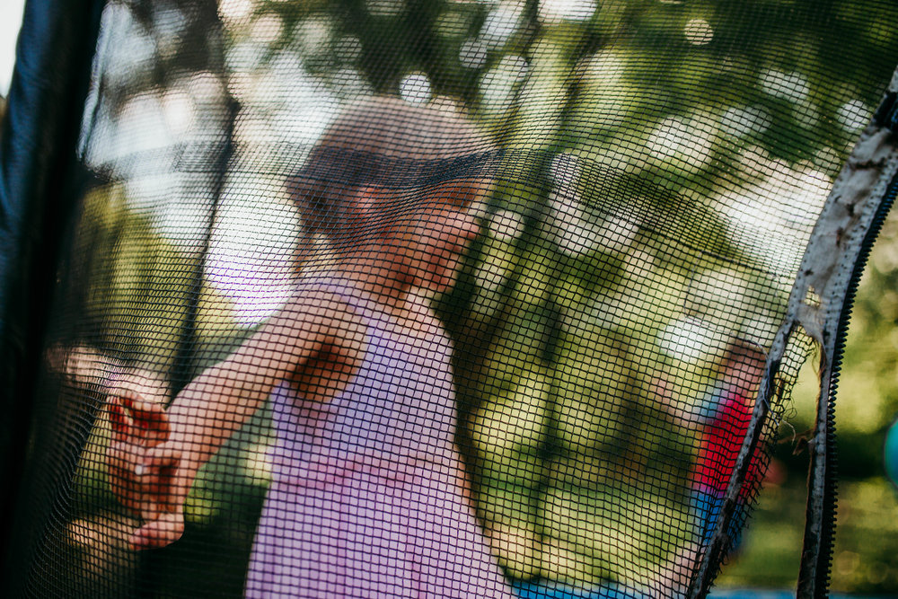 The young girl playing on the trampoline through the net.  The Carter Family : Summer in the Backyard | Hannahill Photography | Kansas City, MO | Family photography lifestyle photographer | Wedding photographer Durham North Carolina Raleigh | Birth photographer Documentary