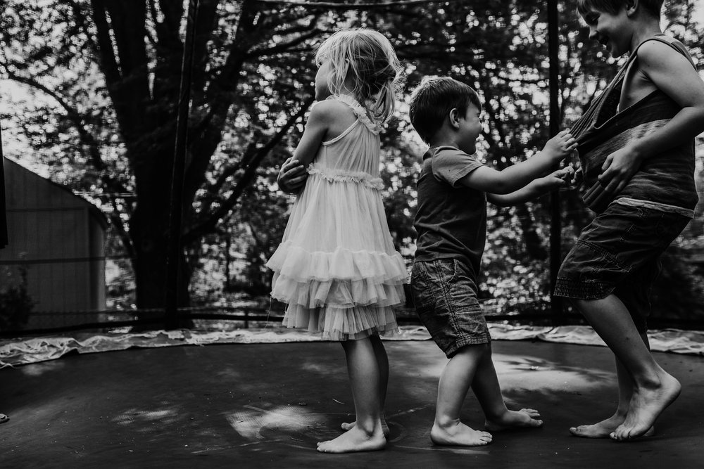 Siblings fight on the trampoline with so much joy in black and white   The Carter Family : Summer in the Backyard | Hannahill Photography | Kansas City, MO | Family photography lifestyle photographer | Wedding photographer Durham North Carolina Raleigh | Birth photographer Documentary