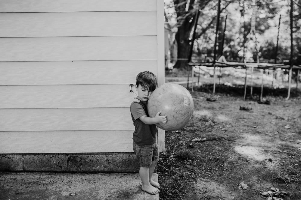 The youngest holds a ball in the backyard protecting it from his siblings, in black and white.   The Carter Family : Summer in the Backyard | Hannahill Photography | Kansas City, MO | Family photography lifestyle photographer | Wedding photographer Durham North Carolina Raleigh | Birth photographer Documentary