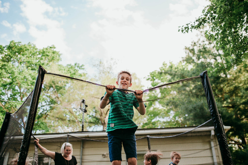 The oldest son jumping on the trampoline from the angle of the top of the trees.   The Carter Family : Summer in the Backyard | Hannahill Photography | Kansas City, MO | Family photography lifestyle photographer | Wedding photographer Durham North Carolina Raleigh | Birth photographer Documentary