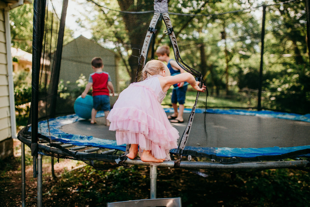 The little girl gets on the trampoline with her siblings.   The Carter Family : Summer in the Backyard | Hannahill Photography | Kansas City, MO | Family photography lifestyle photographer | Wedding photographer Durham North Carolina Raleigh | Birth photographer Documentary
