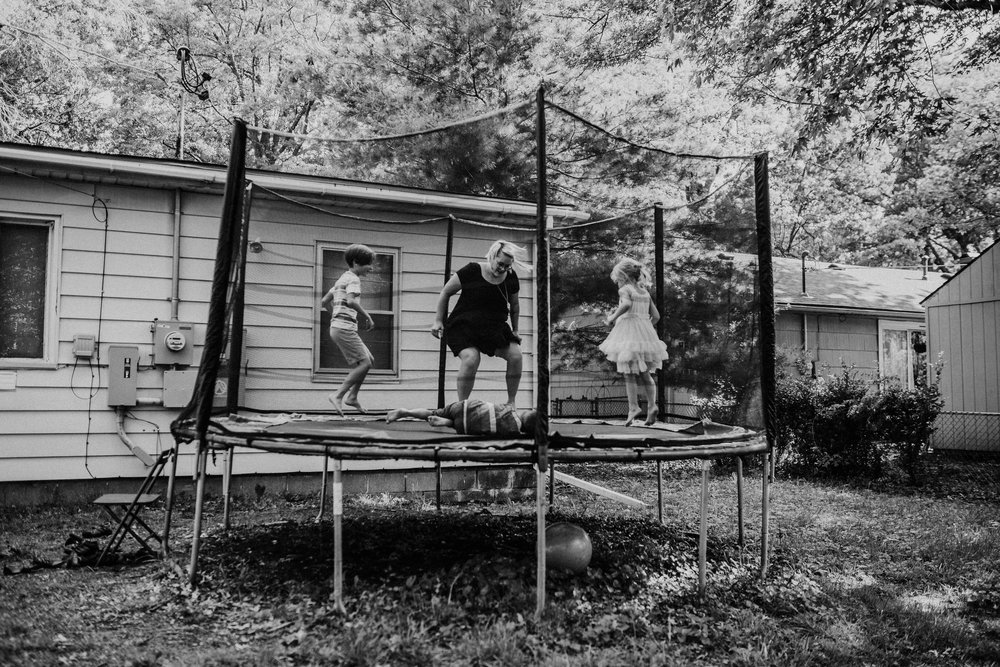 The family bounces on the trampoline in black and white with their first home in the background.   The Carter Family : Summer in the Backyard | Hannahill Photography | Kansas City, MO | Family photography lifestyle photographer | Wedding photographer Durham North Carolina Raleigh | Birth photographer Documentary