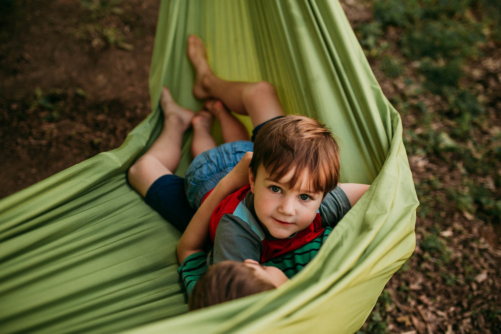 The youngest boy cuddles on the hammock with his brother.   The Carter Family : Summer in the Backyard | Hannahill Photography | Kansas City, MO | Family photography lifestyle photographer | Wedding photographer Durham North Carolina Raleigh | Birth photographer Documentary