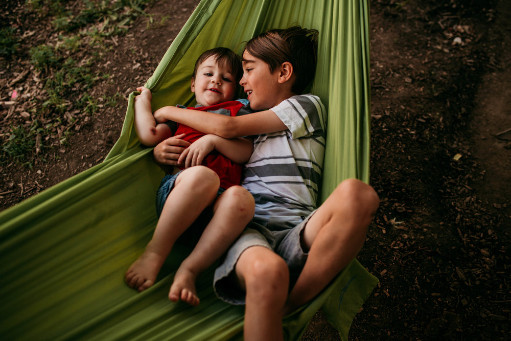 The youngest son and his brother cuddle together on the hammock  The Carter Family : Summer in the Backyard | Hannahill Photography | Kansas City, MO | Family photography lifestyle photographer | Wedding photographer Durham North Carolina Raleigh | Birth photographer Documentary