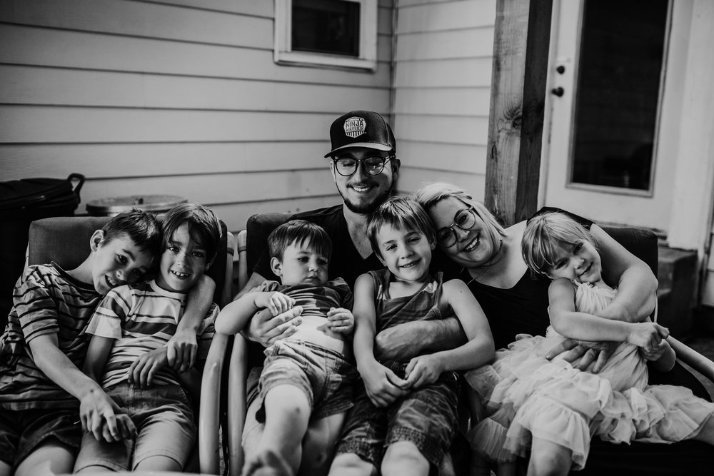 the whole family cuddle together in front of their first home in black and white.   The Carter Family : Summer in the Backyard | Hannahill Photography | Kansas City, MO | Family photography lifestyle photographer | Wedding photographer Durham North Carolina Raleigh | Birth photographer Documentary
