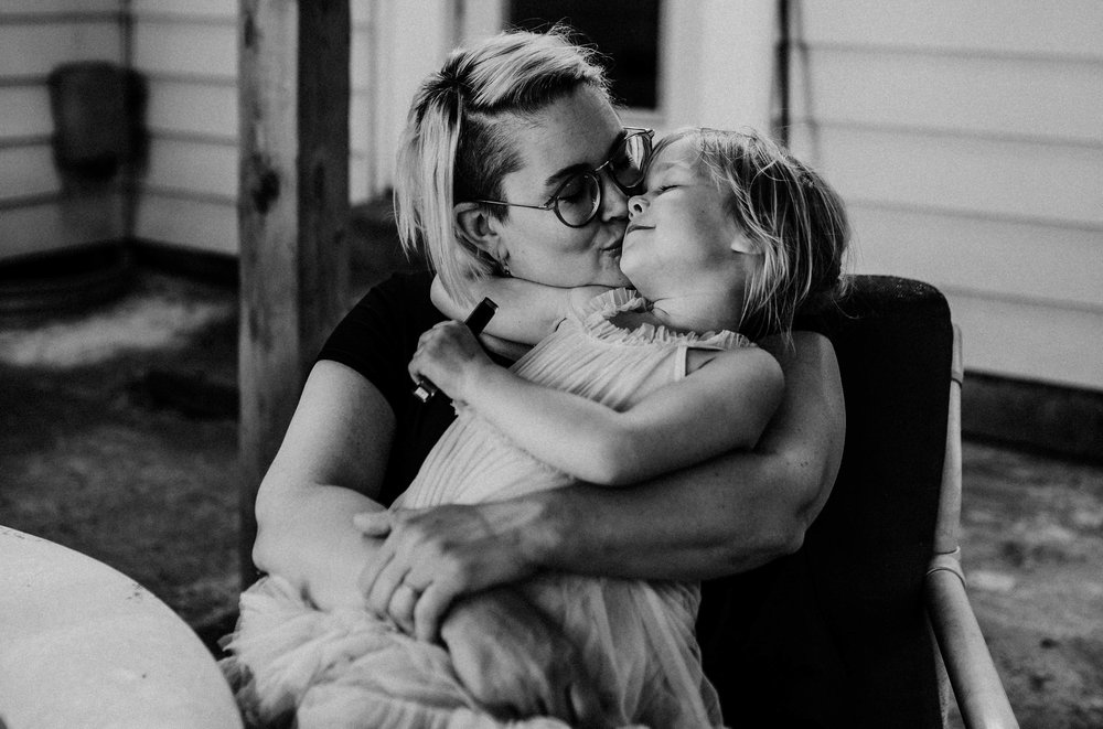 Mom and daughter cuddle together on the back porch in front of their first home in black and white.  The Carter Family : Summer in the Backyard | Hannahill Photography | Kansas City, MO | Family photography lifestyle photographer | Wedding photographer Durham North Carolina Raleigh | Birth photographer Documentary