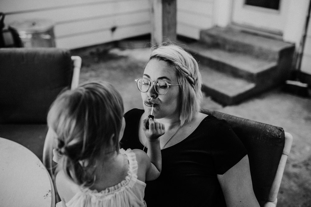 Daughter puts on lipgloss for her mother in black and white.  The Carter Family : Summer in the Backyard | Hannahill Photography | Kansas City, MO | Family photography lifestyle photographer | Wedding photographer Durham North Carolina Raleigh | Birth photographer Documentary