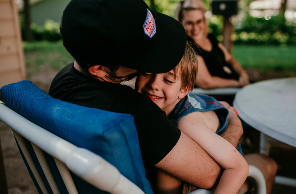 Dad cuddles their little wild man son in a mom of calm.   The Carter Family : Summer in the Backyard | Hannahill Photography | Kansas City, MO | Family photography lifestyle photographer | Wedding photographer Durham North Carolina Raleigh | Birth photographer Documentary