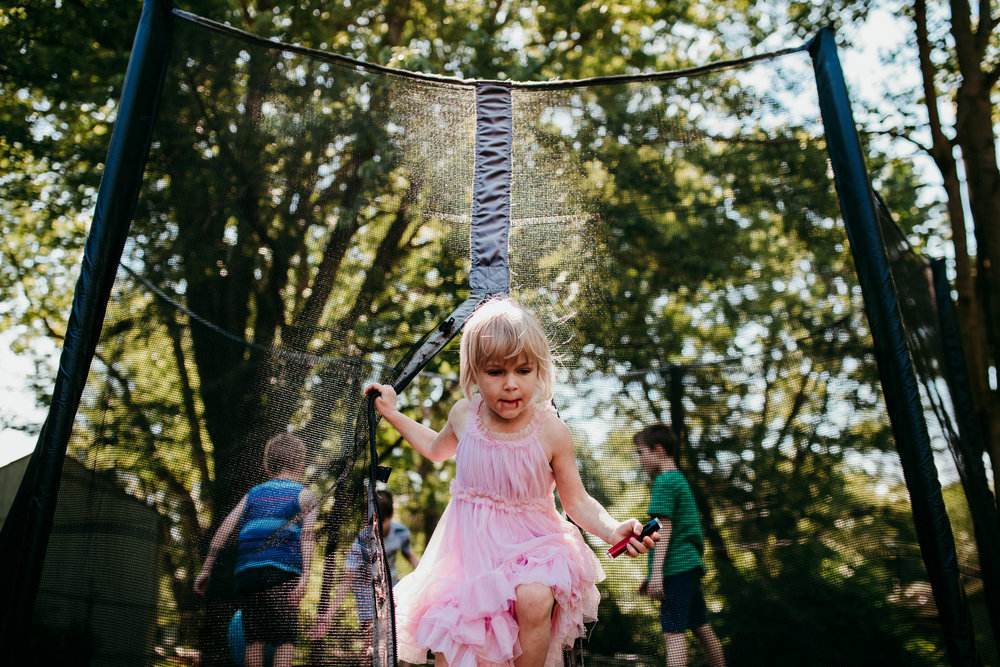 Little girl climbing out of the trampoline zipper  The Carter Family : Summer in the Backyard | Hannahill Photography | Kansas City, MO | Family photography lifestyle photographer | Wedding photographer Durham North Carolina Raleigh | Birth photographer Documentary
