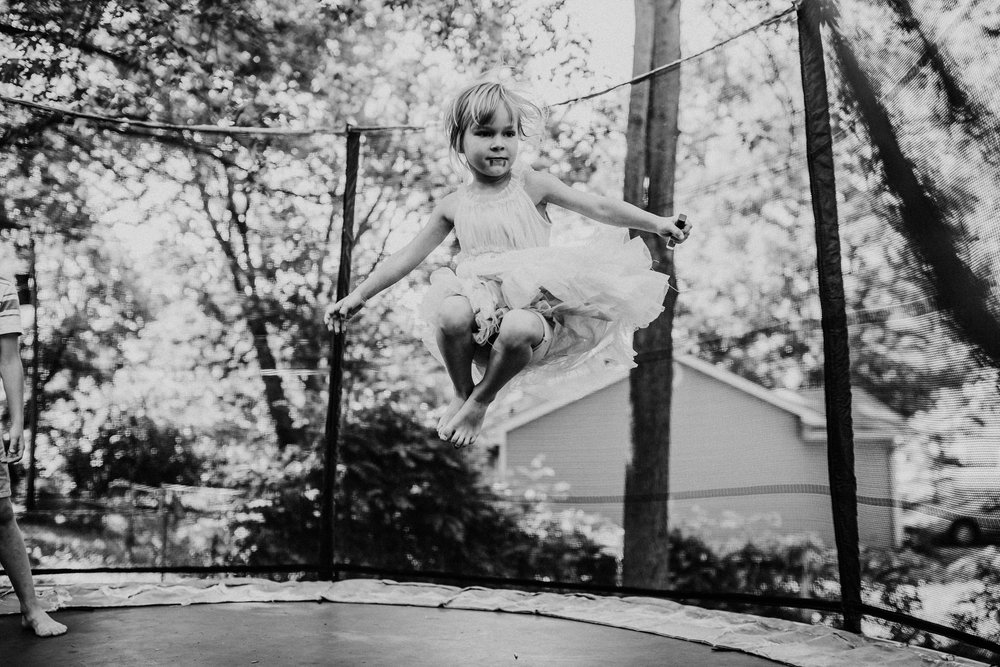 The little girl jumps high in black and white  The Carter Family : Summer in the Backyard | Hannahill Photography | Kansas City, MO | Family photography lifestyle photographer | Wedding photographer Durham North Carolina Raleigh | Birth photographer Documentary