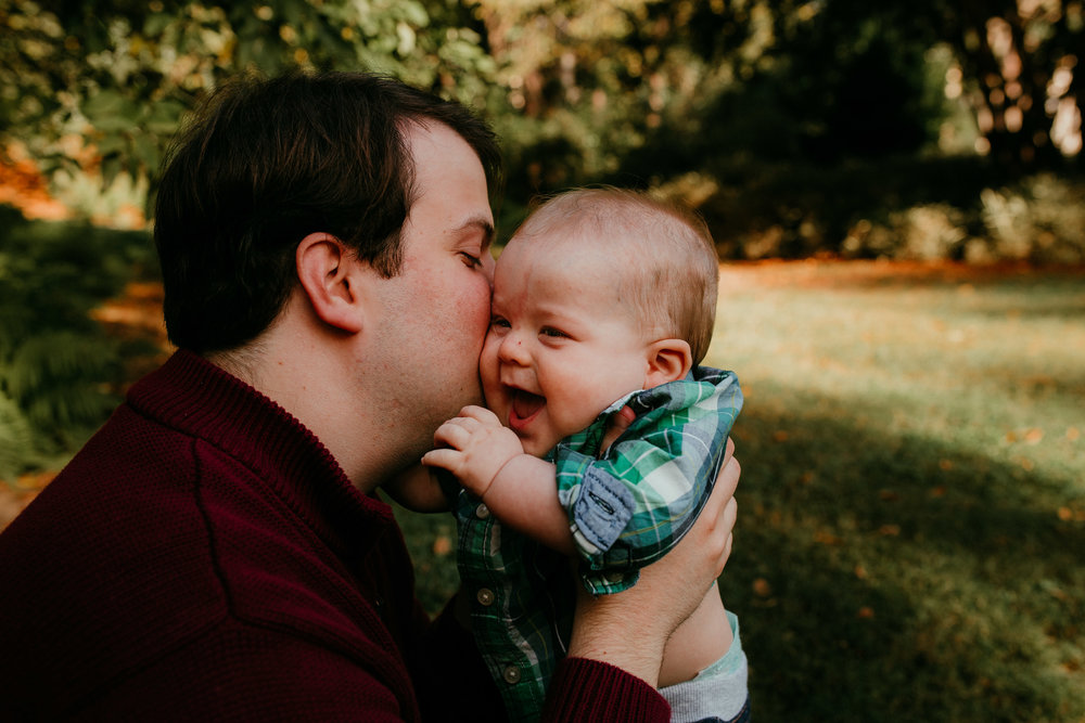 Dad gives baby kisses on the cheek to make him laugh during a family session at SP Duke Gardens in Durham, NC | Hanna Hill Photography | Raleigh birth and Family photographer