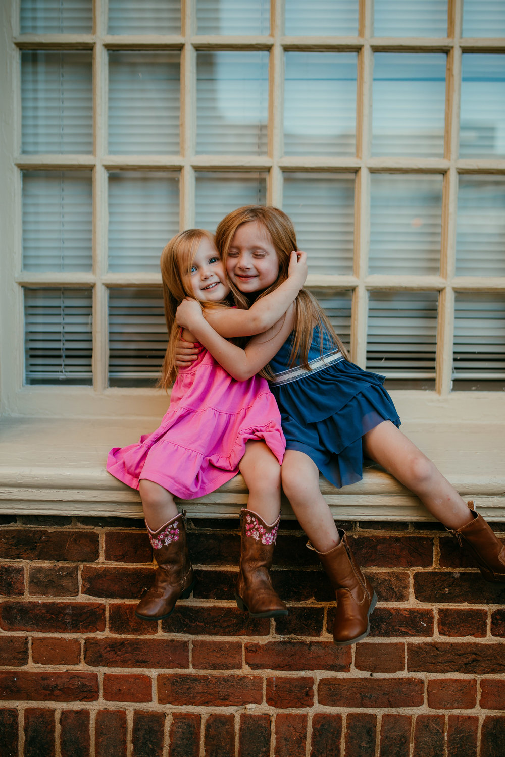 two sisters sitting on a window sill during their downtown durham, NC family photography session | Hanna Hill Photography | Raleigh birth and family photographer