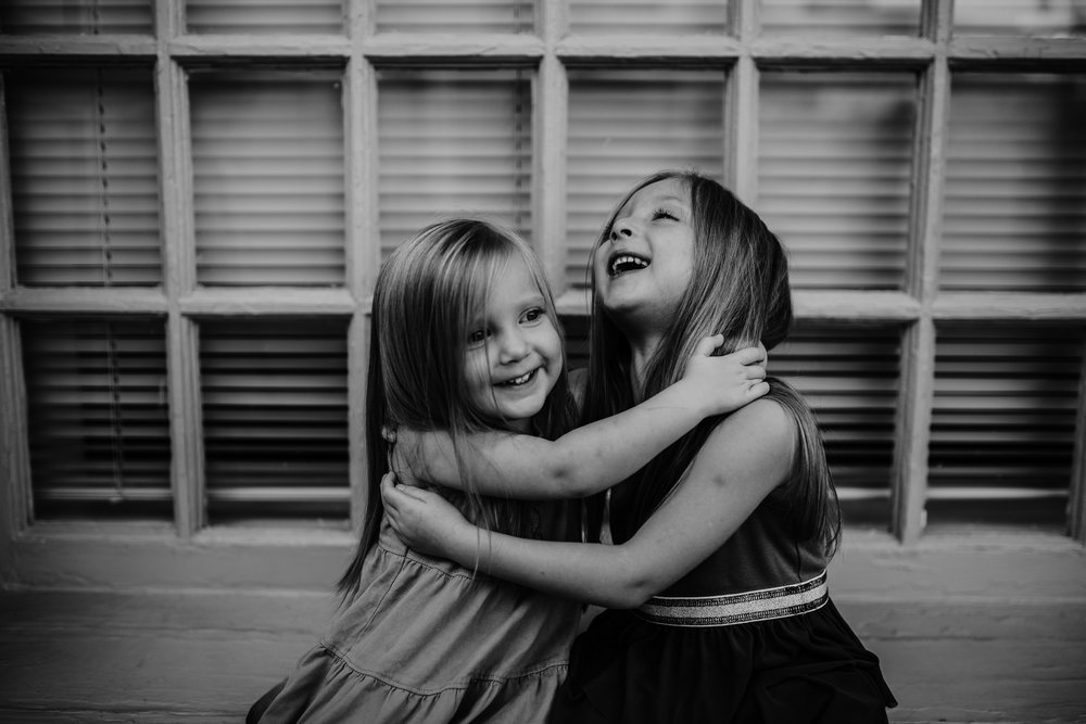 sweet sister moment on a window sill during their downtown durham, NC family photography session | hanna Hill photography | Raleigh birth and family photographer