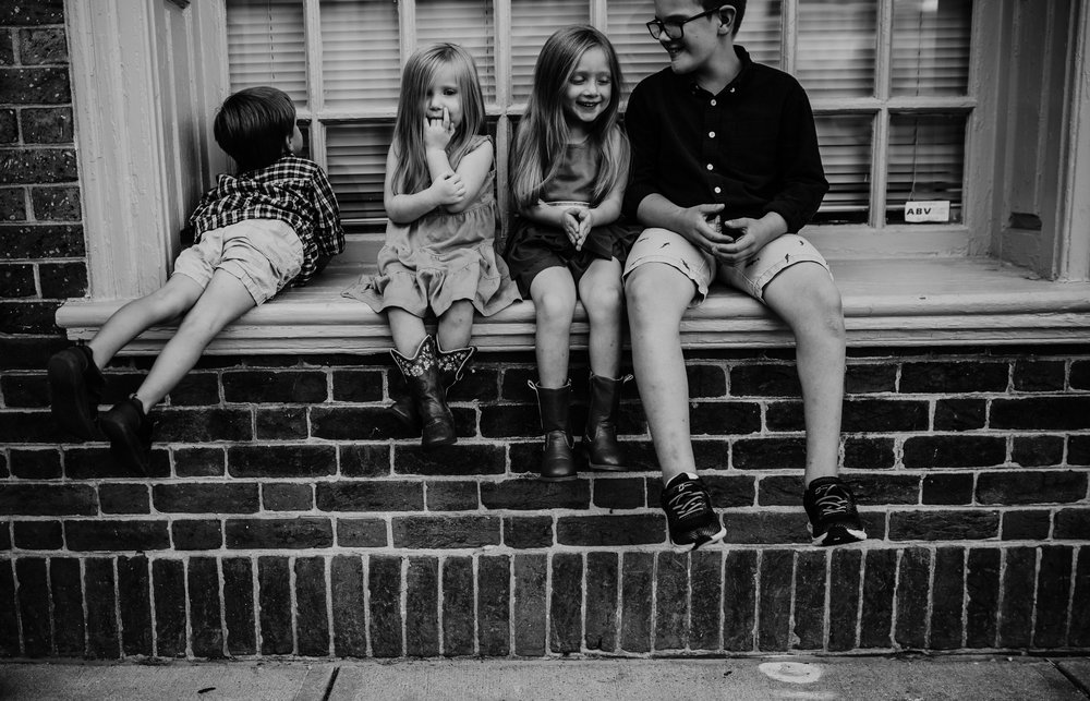 the siblings sit on a window sill during a downtown family session in Durham, NC | Hanna Hill Photography | Raleigh birth and family photographer