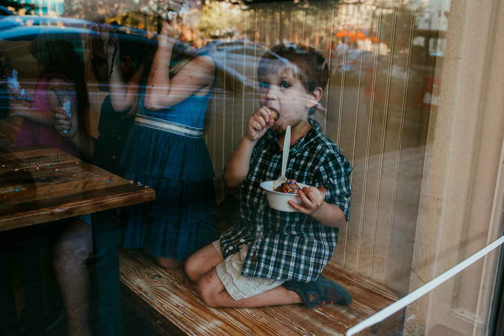 siblings eating ice cream though the window at the Parlous ice cream shop during their downtown durham, NC family photography | Hanna Hill Photography | Raleigh birth and family photographer