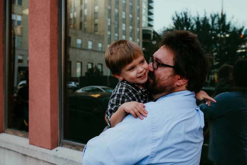 father and son cuddle moment in front of the window during a downtown durham, NC family photography session | hanna Hill photography | Raleigh birth and family photographer