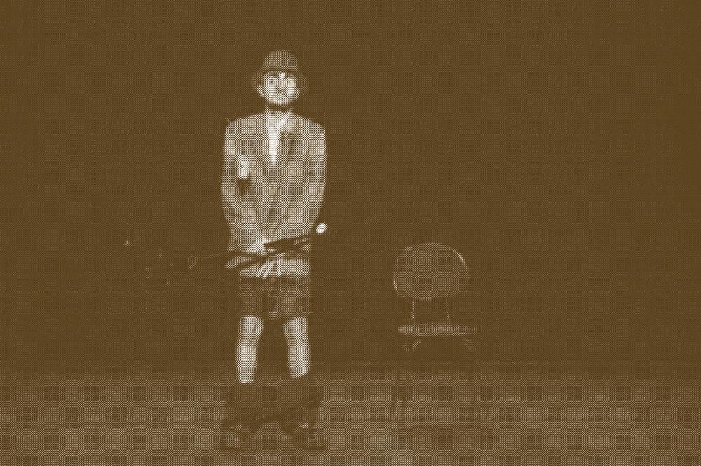 Ator vestido de chapéu, terno e calças caídas, ao lado de uma cadeira no palco.