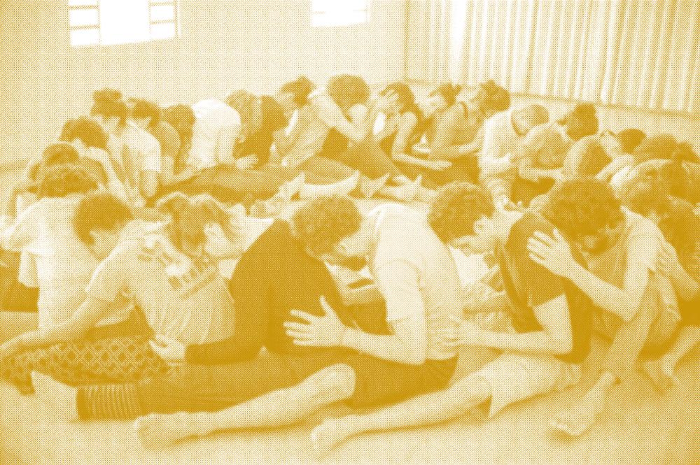 Grupo de pessoas sentadas em círculo, uma atrás das outras, encostando cabeça nas costas da pessoa da frente, está é uma técnica do contato improvisação.