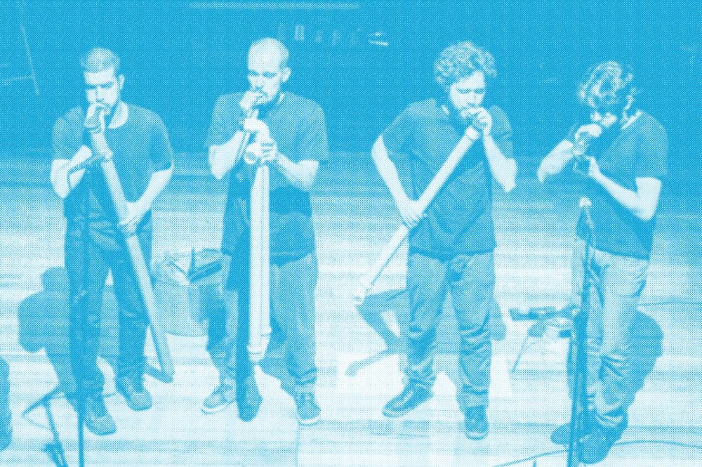 Quatro integrantes do Grupo Vida Seca tocando instrumentos feitos de lixo.