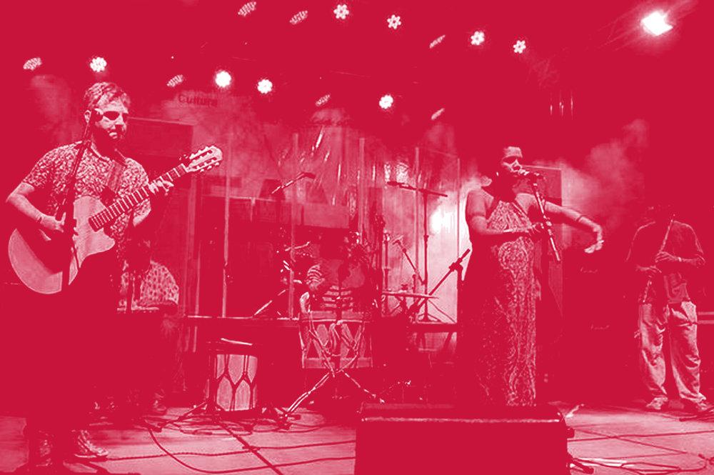 Homem toca um violão e uma mulher canta junto a um microfone em pedestal enquanto movimento os braços.Ao fundo outros músicos e instrumentos de percussão.