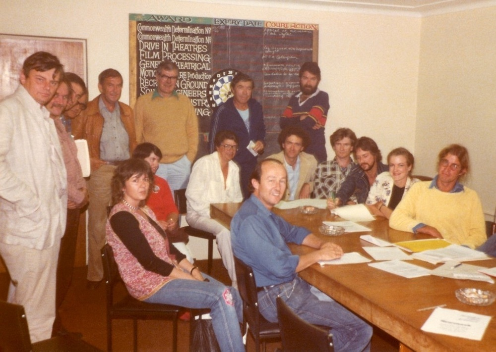 A photograph was taken at the meeting in 1981 to set up the original articles of Association. From left to right: (Standing) Michael Thornhill, Albie Thoms, Richard Michalak, Eric Gross, John Power, David Baker, Michael Pate, Bert Deling. (seated) Tom Jeffrey, Linda Blagg, Di Drew (in red), Henri Saffron, Tom Cowan, Chris Noonan, Ian Barry, Gillian Armstrong, James Ricketson. Behind the camera, Phil Noyce. (Absent; Esben Storm, Carl Shultz, Stephen Wallace, John Duigan.)