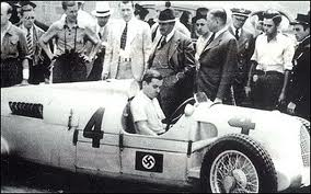 Nuvolari was late for practice. A mechanic warms his C-type Auto Union. Its designer Dr Ferdinand Porsche (behind cockpit) looks on.