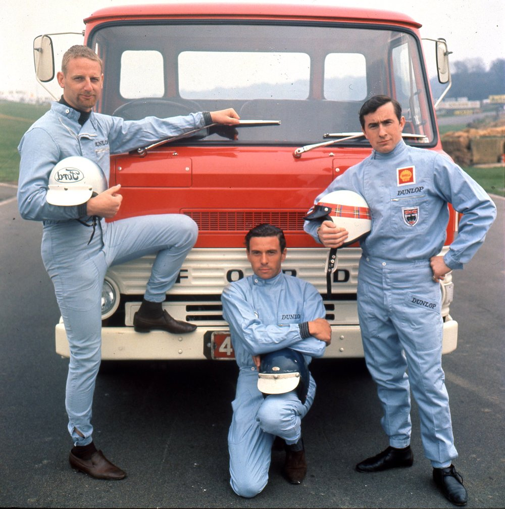 Ambassadors for sport. John Whitmore on the left had the FORD on his helmet painted in reverse ostensibly so that drivers ahead could read it in their rear-view mirror. Publicity picture for Ford trucks with Clark and Jackie Stewart short-haired and 1960s early in his grand prix career.