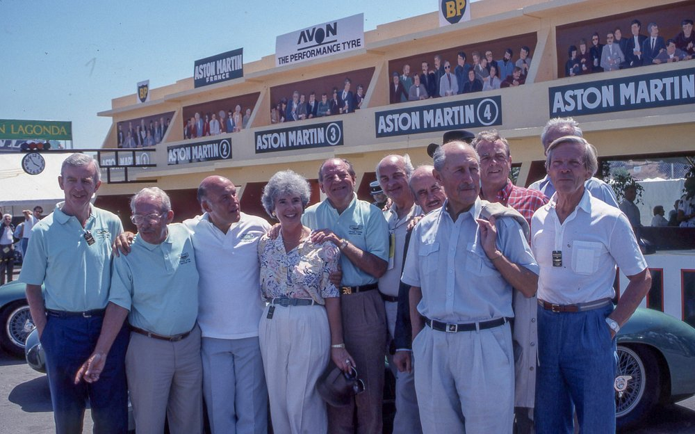 Left to right. Tony Brooks, Sir David Brown, Sir Stirling Moss, driver and writer  Denise McCluggage , Innes Ireland, not known, Maurice Trintignant, Jack Fairman, Phil Hill 1961 world champion driver and Aston Martin team member, Paul Frére.