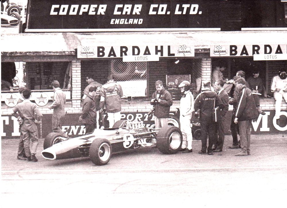 Cooper transporter was parked in the paddock behind the pits. Graham Hill sits on the Lotus pit counter on right. The picture must have been taken from the grandstands opposite.