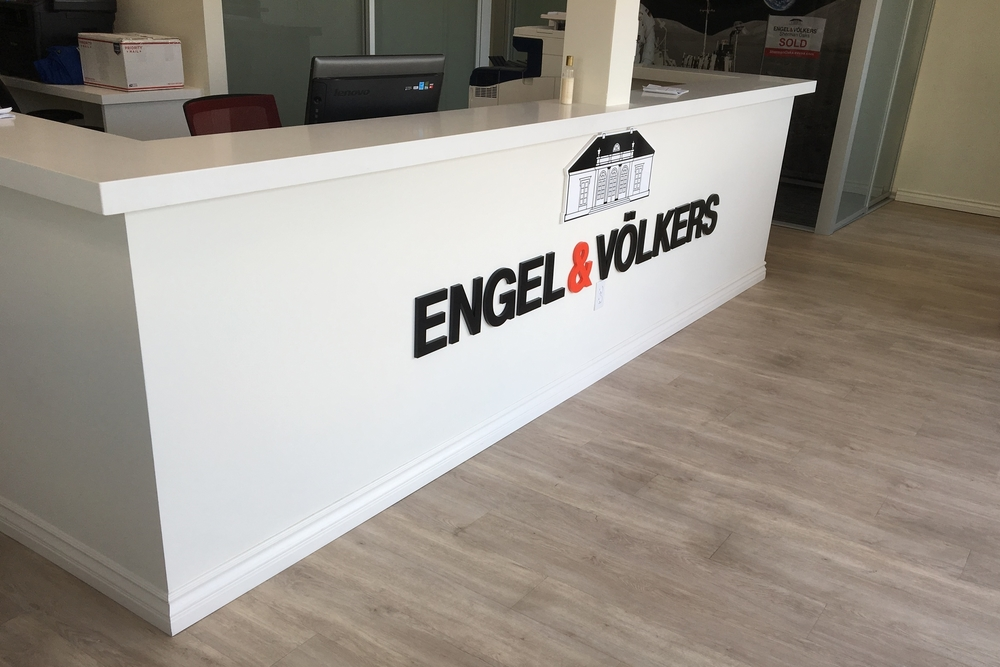 "Premium Sign Solutions fabricated and installed a dimensional lobby sign and a custom dimensional logo for Engel & Völkers in Encino. The sign was created using 1/2"" thick laser cut acrylic dimensional letters and a matching 1/2"" thick acrylic dimensional Villa, with a digital print applied to the face. We installed the signage to the front of the reception desk at their Encino location. The sign creates instant brand recognition and the red ampersand against the white reception desks adds depth and flair to the entry way. Engel & Völkers is a leader in the sale of residential and commercial real estate, resorts, yachts, and private jets in the premium segment. Founded by Christian Völkers in 1977 as a boutique shop delivering high-end services to an exclusive clientele, today they are a luxury brand recognized around the world for our culture of exclusivity, competence and passion."
