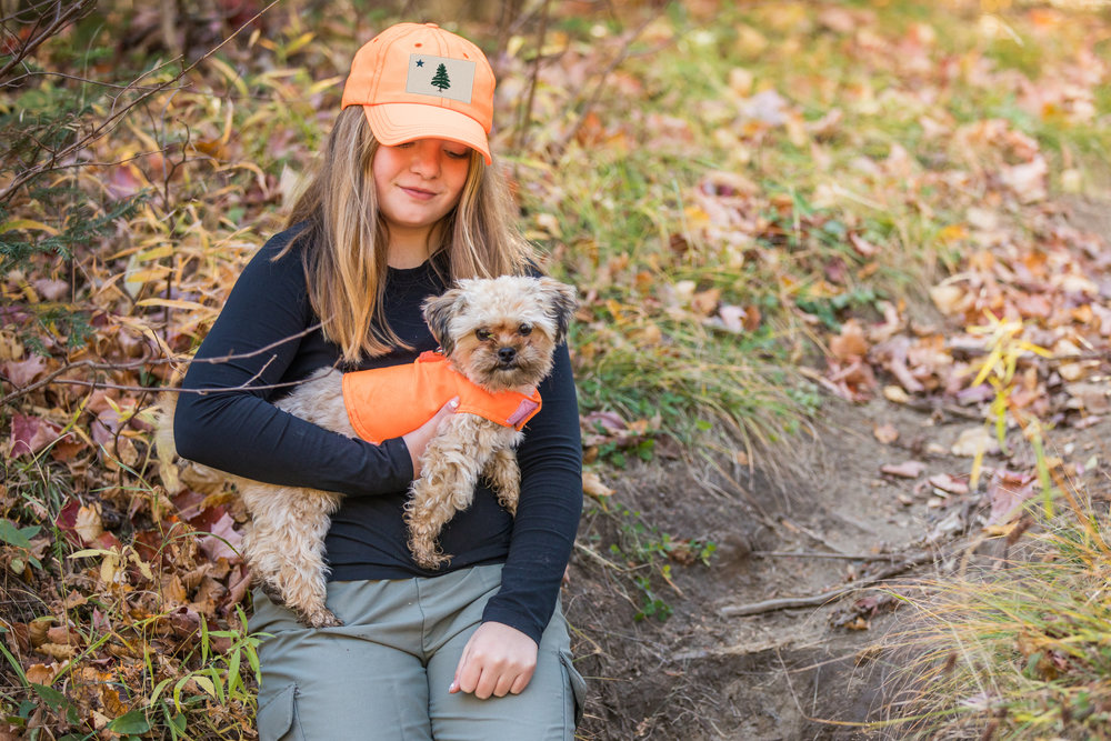 Dog Not Gone and No Fly Designs make insect repelling clothing for kids and pets. Here the owner's daughter wears a No Fly Zone Baseball Cap with the company's  1901 Original Maine Flag  embroidered onto it, and their dog wears a Mini Safety Dog Vest for visibility in the woods.