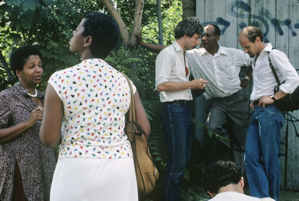In this image: (from left to right) Joan Maynard, Marcia Goldman, Rex Curry, Unidentified man, and William Carey, taking a rest from leading a restoration tour of the Hunterfly Road Houses. James G. Hurley Slide Collection, 5th of July Resource Center for Self-Determination & Freedom, Weeksville Heritage Center.