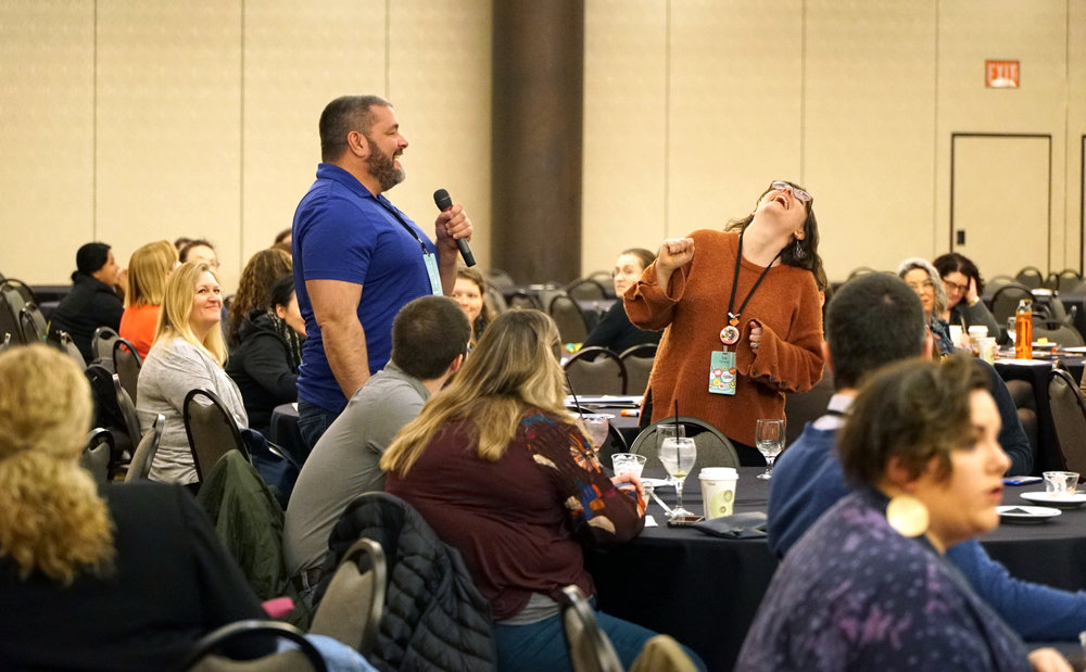 Two librarians laughing while speaking in a microphone to a group.