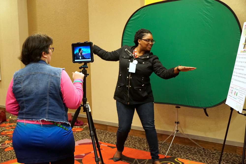 Two librarians--one in front of a green screen, the other operating an iPad.