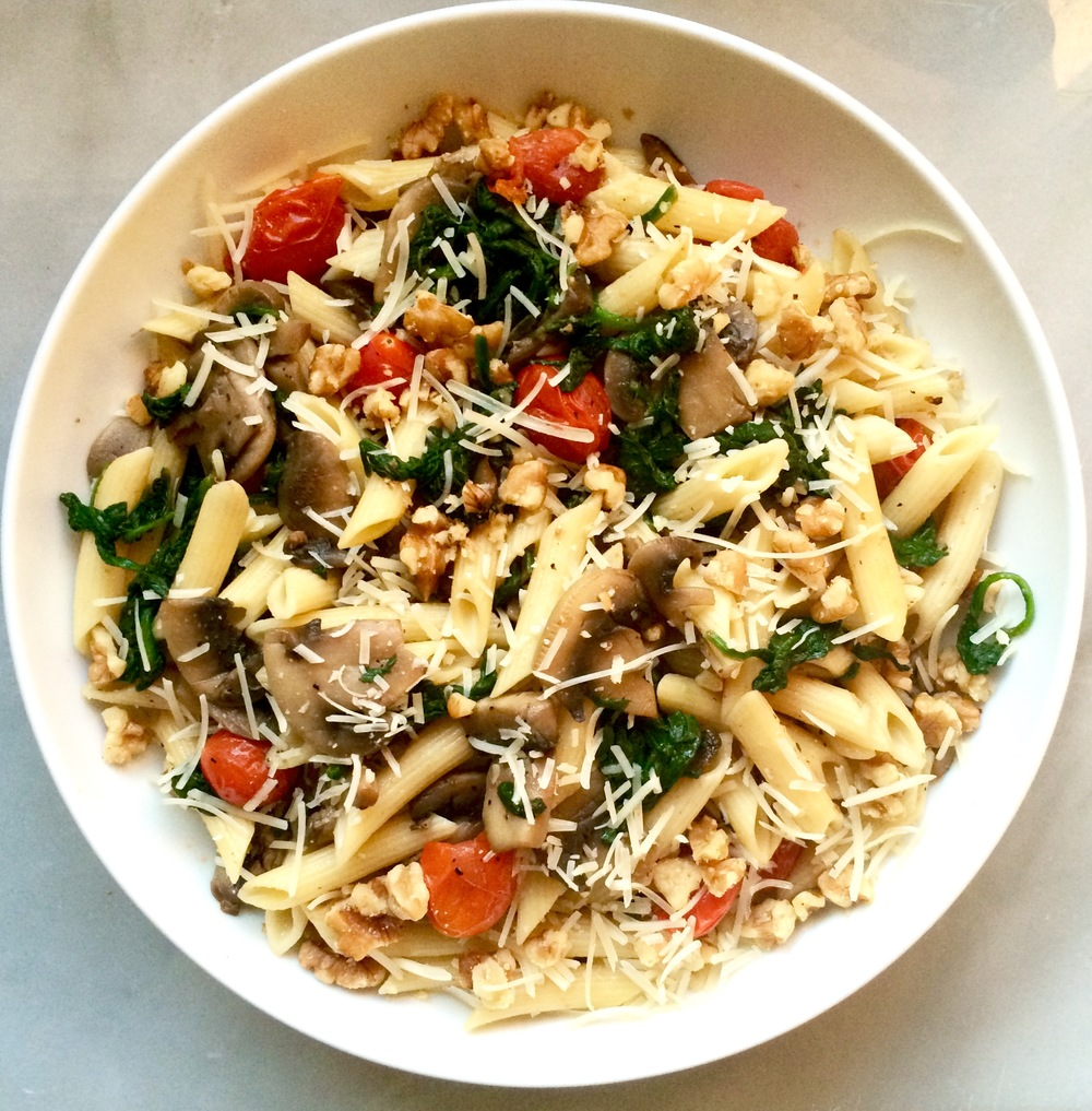 Pasta with mushrooms, spinach, and tomatoes, with a garnish of walnuts and parmesan