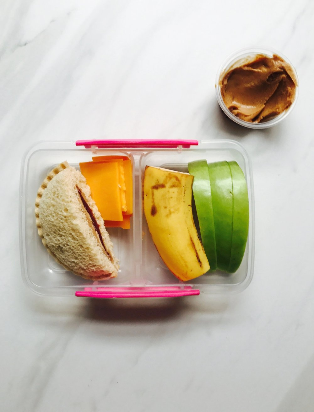 Smuckers PB & J  uncrustables , cheddar cheese slices, banana, green apple, and peanut butter. Little plastic containers are great when you need just one more thing to keep your kid satisfied.