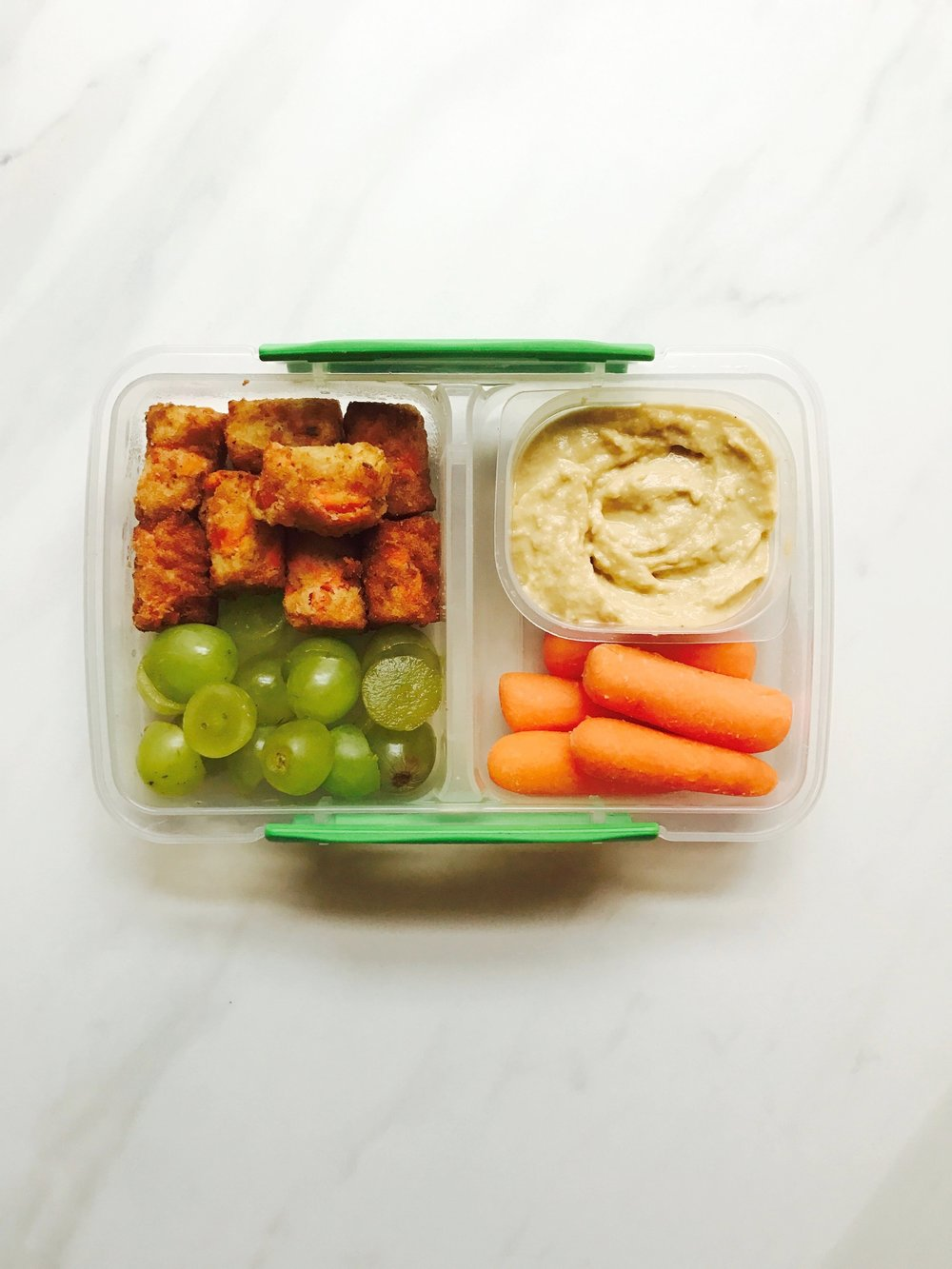 Dr. Praeger  carrot puffs , green grapes, hummus, and baby carrots.