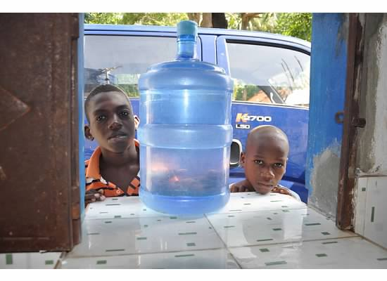 Children pick up a jug of clean water at the Ascension Church and School's facilities.