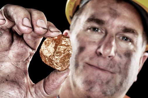 Photo of a miner with a gold nugget used for everything from jewelry to dental scrap to circuit boards, which can all be recycled by GoldRefiners.com, part of Specialty Metals Smelters & Refiners.