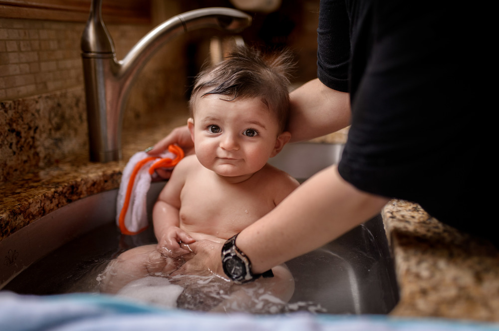 Baby Getting Bath In Kitchen SInk