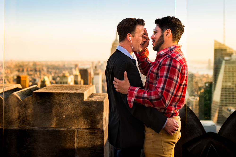 Man Affectionately Touching Man's Face on Top of The Rock
