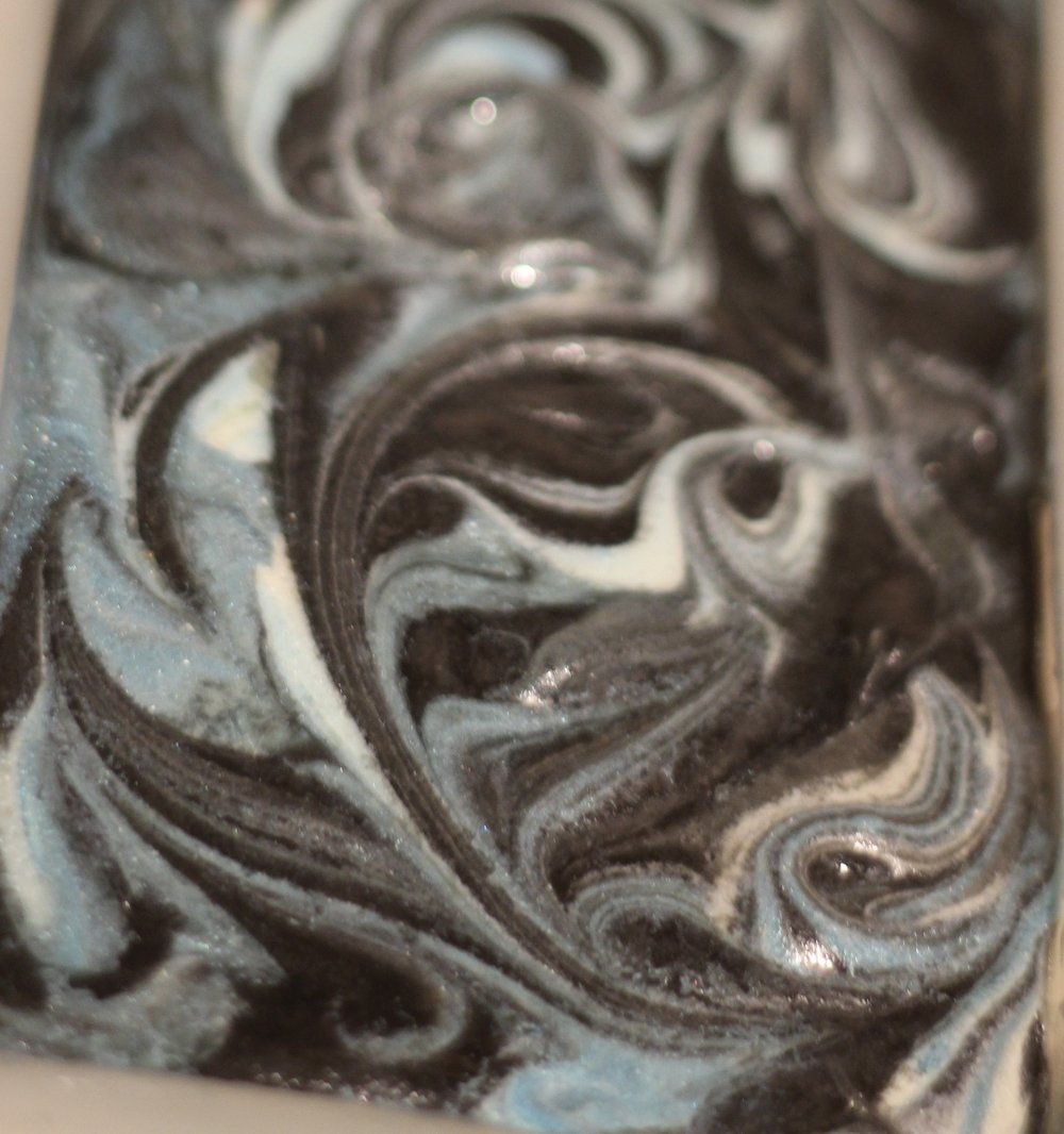 - This is a new batch of soap colored with activated charcoal with a touch of blue and white swirled in.  It is scented with Wasabi fragrance oil which is a nice clean scent for a man or woman. I will post pictures of it cut soon.