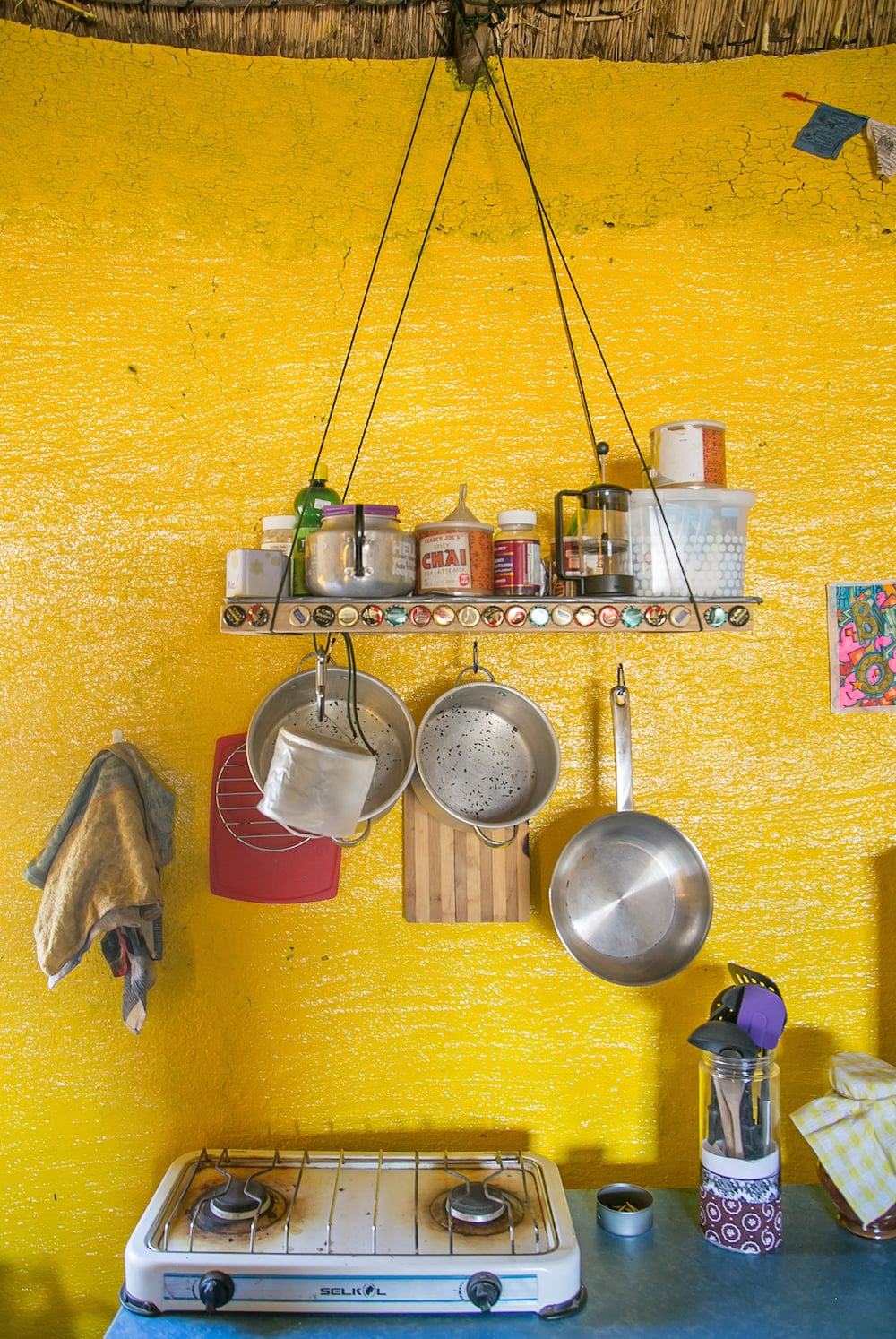 My Pot Rack   What I Used: Strong Paracord (brought from the US), small carabiners as hooks, 4 pieces of 2in. x 2in. wood to build the frame, an old mop sawed into four pieces to make the perpendicular rows where things are hung, Mpowered light, flat board to create the shelf, and nails!          Cost: $20