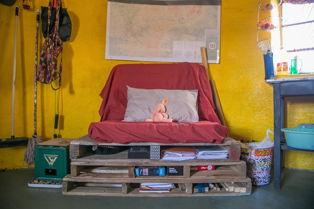 Welcome to my Living Room!   What I Used: Inherited from an RPCV the actual couch is a crash pad for bouldering (unfortunately, most of the rock is in the lowlands..) A fitted sheet, 3 pallets - that double as storage, a pillow and pillowcase, and a Maluti Mountain Brewery Crate as a table.                    Cost: $15
