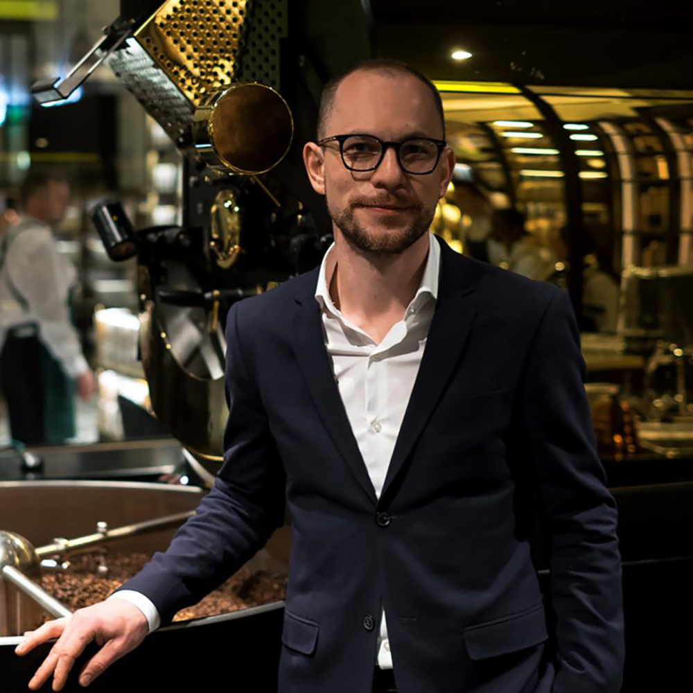 Bartosz Ciepaj - EventsBartosz is currently Master Roaster at Harrods and supported the launch of the new Roastery and Bake Hall in 2017. Bartosz oversees the roasting, develope profiles, creates coffee blends and Q&C. In addition to his role as Master Roaster, Cipeaj trains Harrods Baristas' on the necessary ways to prepare coffees to the Harrods standard level of quality across all 26 cafes and restaurants at Harrods.What's your position within the Working Group? Chairman of the Event CommitteeWhat are your ambitions for BGE? To champion the work and innovation of Baristas across the world.What are your personal coffee ambitions for 2018? I look forward to continuing my role managing the Harrods Barista Training Academy and watching new Baristas join the field and develop their passions within the world of Coffee. I wish to continue experimenting and developing new coffee blends at Harrods and introducing our customers to a variety of new flavours they have yet to explore. Aside from my role at Harrods, I hope to further develop my cupping experience to become the Juror for the Cup of Excellence. There are also some very interesting plans for BGE events next year which I am already excited about.Espresso...single origin or blend? Single