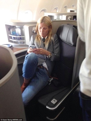 Gwyneth traveling 1st class and on her phone.