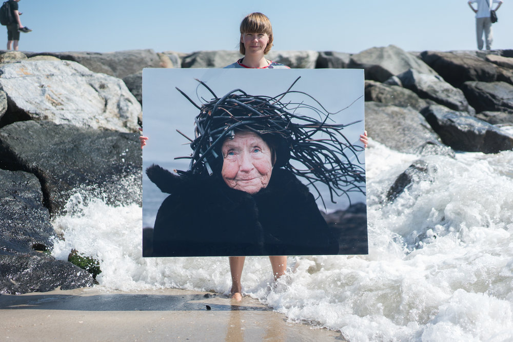 Riitta Ikonen holding a work from the series Eyes as Big as Plates (Agnes II, Norway 2011) at the Rockaway Beach in September 2017. Photo by Liisa Jokinen.