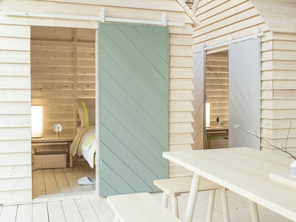 """The  Koti Sleepover  installation in 2017 brought the Finnish cabin experience to the  Institut Finlandais  in Paris. With Koti (Finnish for """"home"""") Bergroth wanted to highlight the Finnish way of sharing: guests were invited to sleep in wooden cabins and share meals around a communal table. Photo: Kaapo Kamu."""