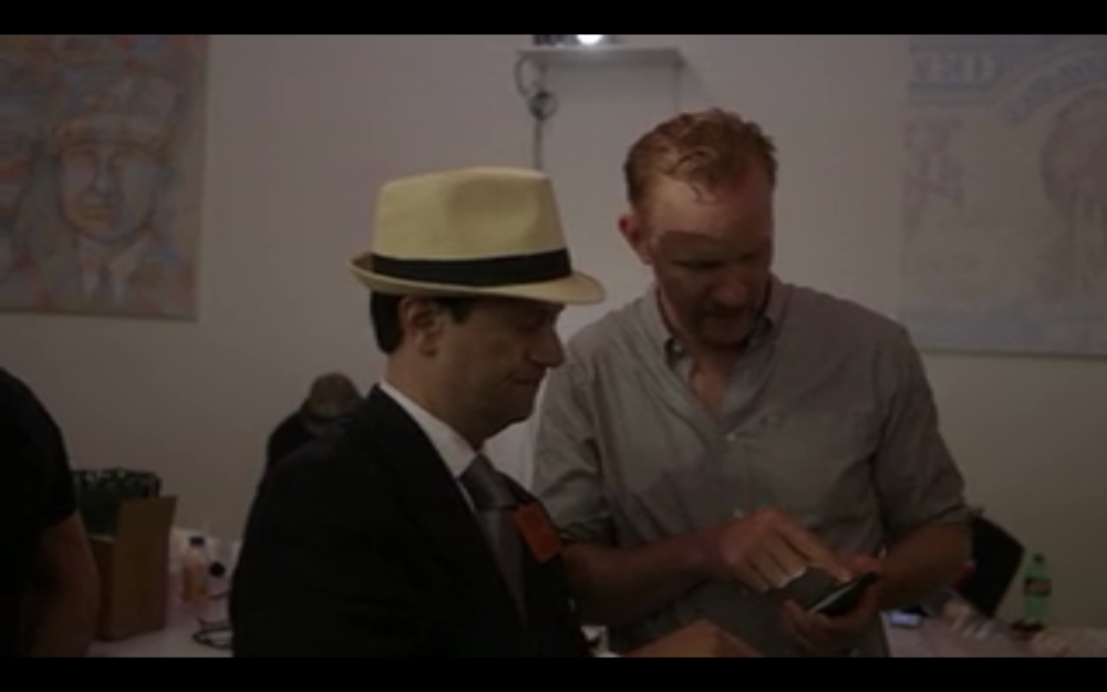 Morgan Spurlock buys his first Bitcoin at the Bitcoin Center, while Jenna Lash's works can be seen in the background.