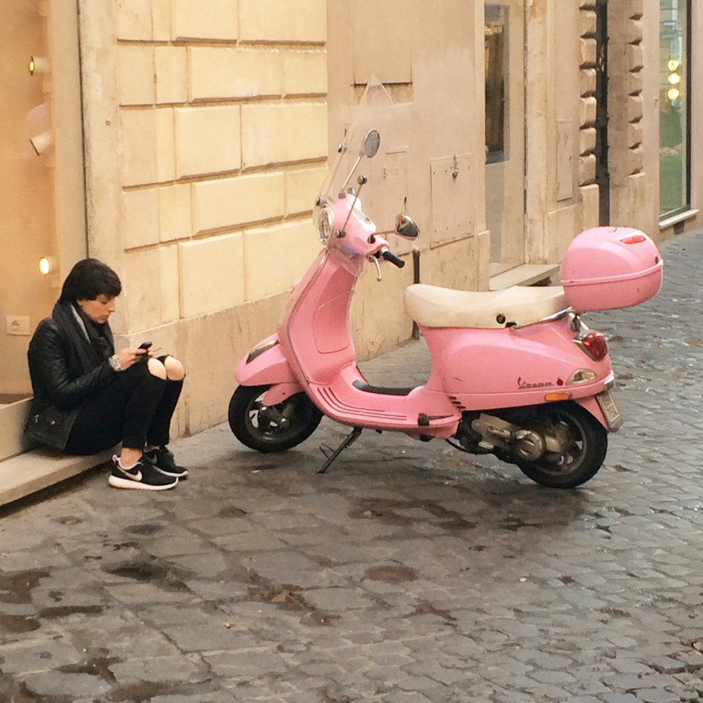 Street shot of pink Vespa in Rome